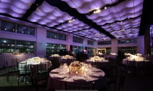 Round Tables set for dinner with purple lighting and candles on the tables