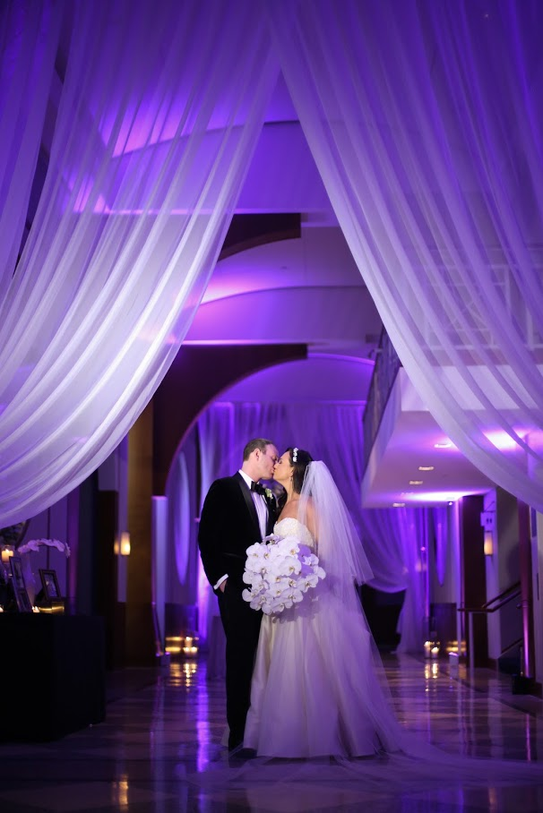 Bride and Groom kissing in the gallery standing
