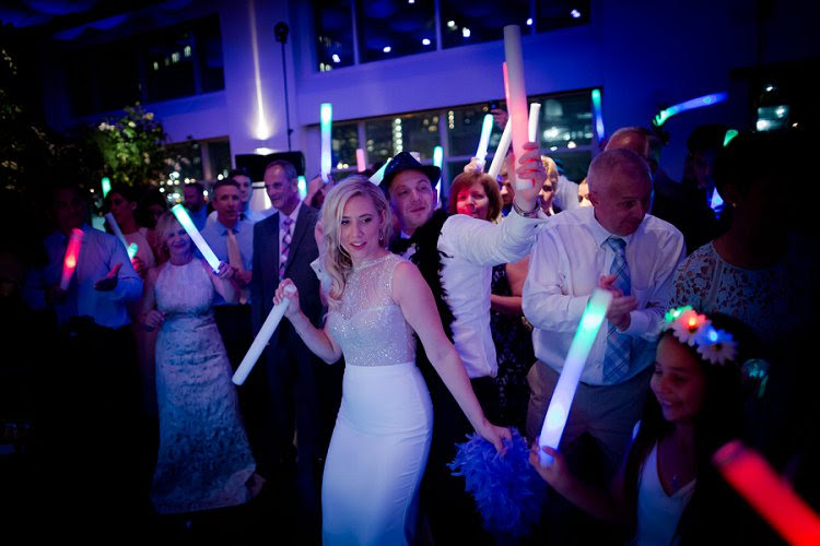bride and guests on the dancefloor playing with flowing sticks