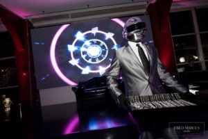 DJ wearing a robot like mask. Lights in the background