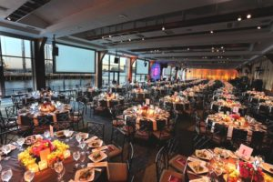 Round Tables set for dinner. Screens displaying presentations