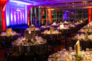 Candlelit tables with floral arrangement, stage