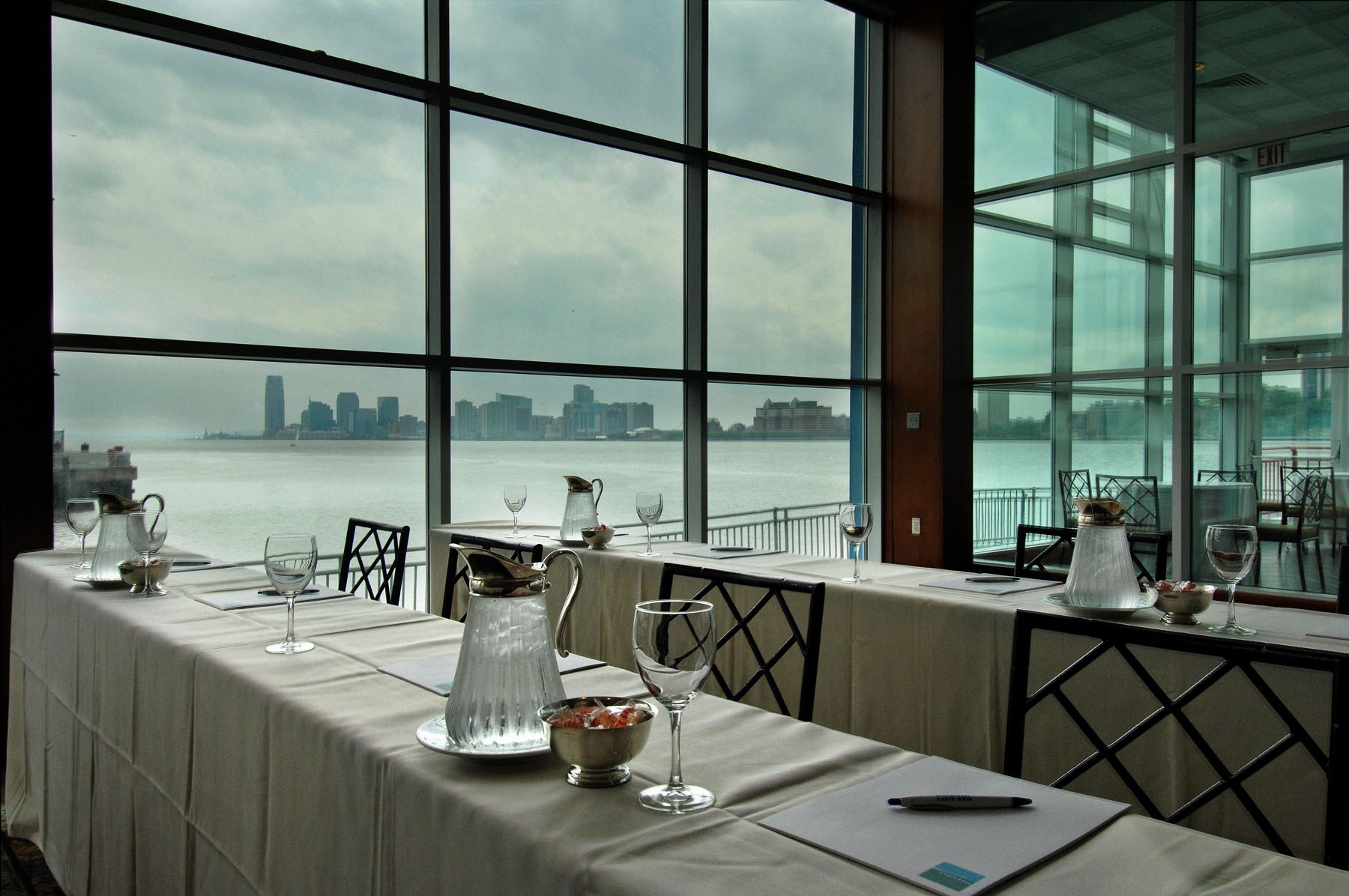 Pier Sixty in a classroom set up, note pads, pens, water service on the tables with water views in the background