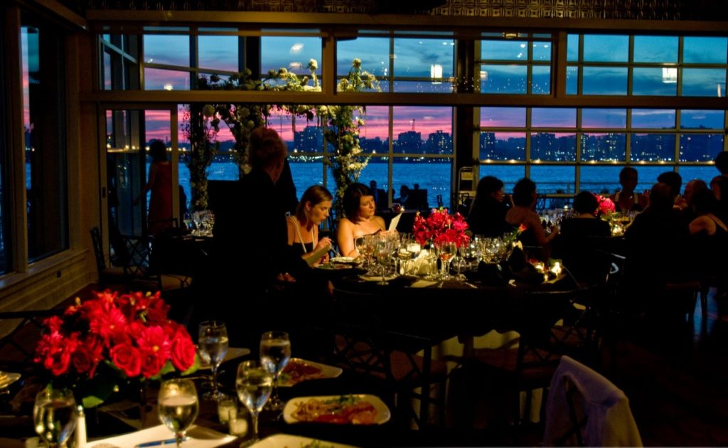 Pre set first course on the tables, guests starting to sit down, sunset in the background and hudson river