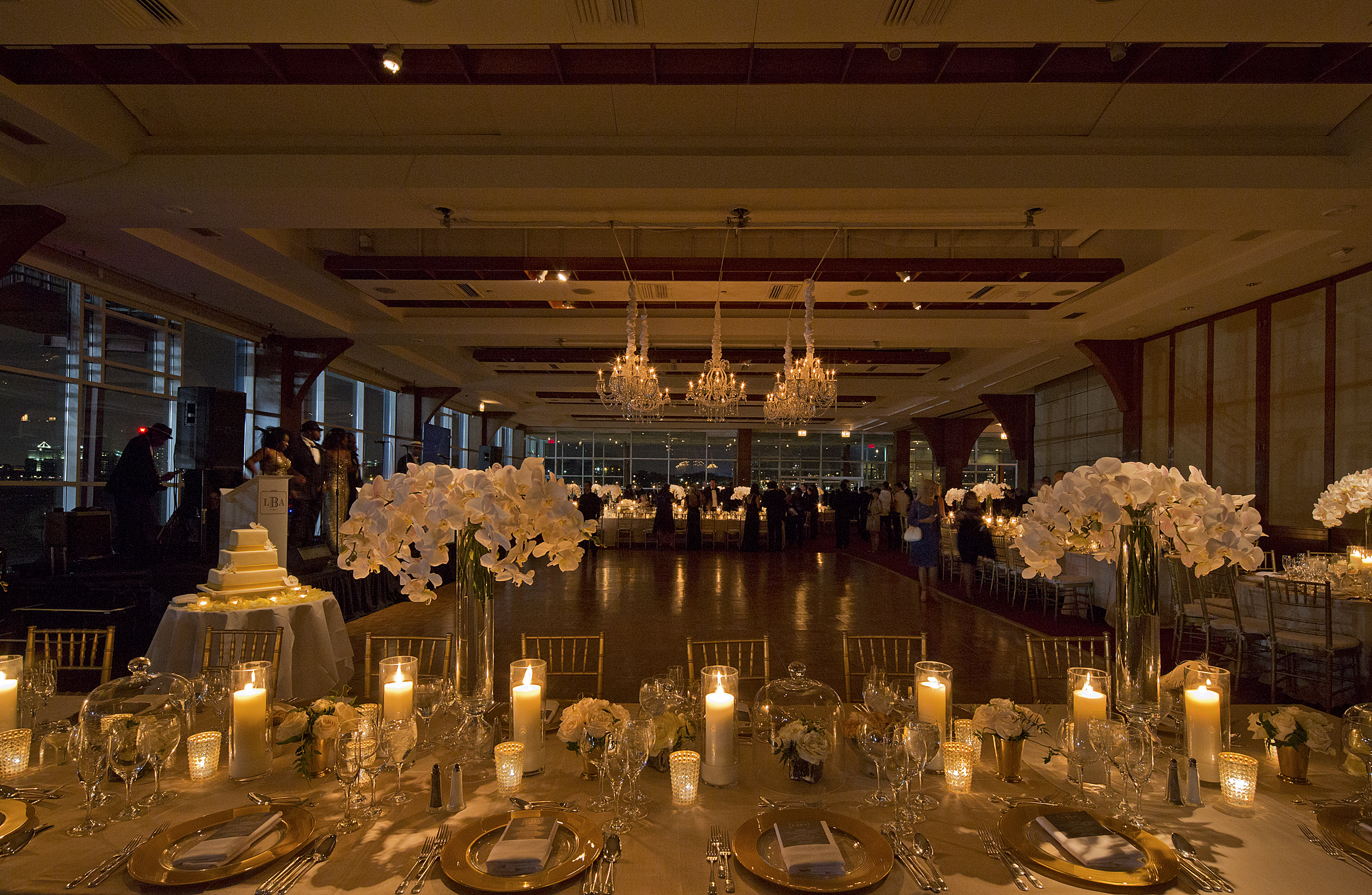 Pier Sixty set up with a dance floor and a mix of rectangular and round tables with candles, white flowers and a band on stage on the left.
