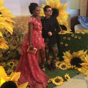 Couple poses in front of sunflowers