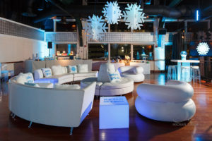White sofas and fund decor items hanging from the ceiling