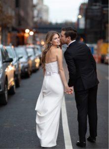 Groom kissing bride in street