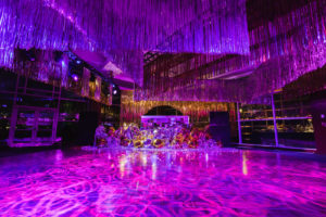 Tinsel hangs above purple-lit dance floor