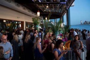Guests drink cocktails outside by the waterfront