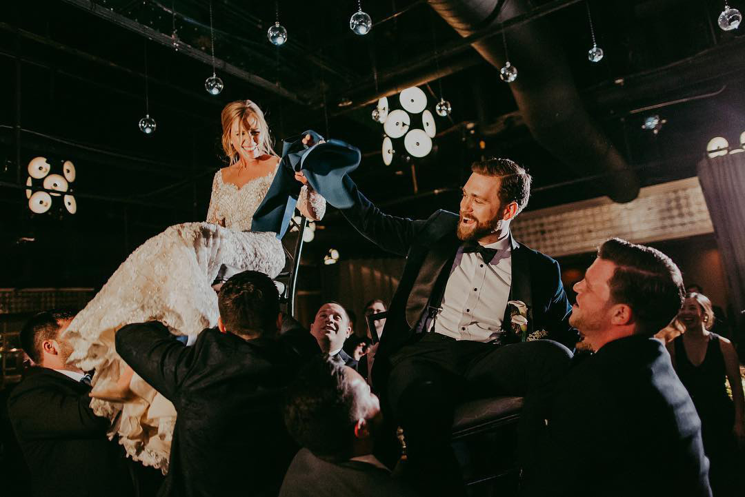 Newlyweds laughing as they crowdsurf in chairs