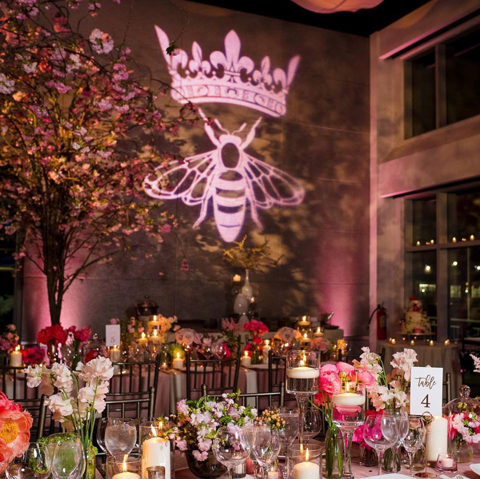 Queen bee logo projected onto wall above dinner tables