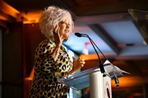 Woman in leopard print shirt speaks at podium