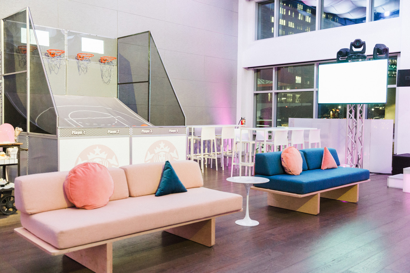 Pastel couches with geometric pillows in front of basketball game.