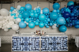 Tie-dyed bar counter in front of giant blue balloon decorative wall.