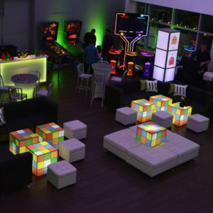 Seating area with giant Rubik cube and arcade games.