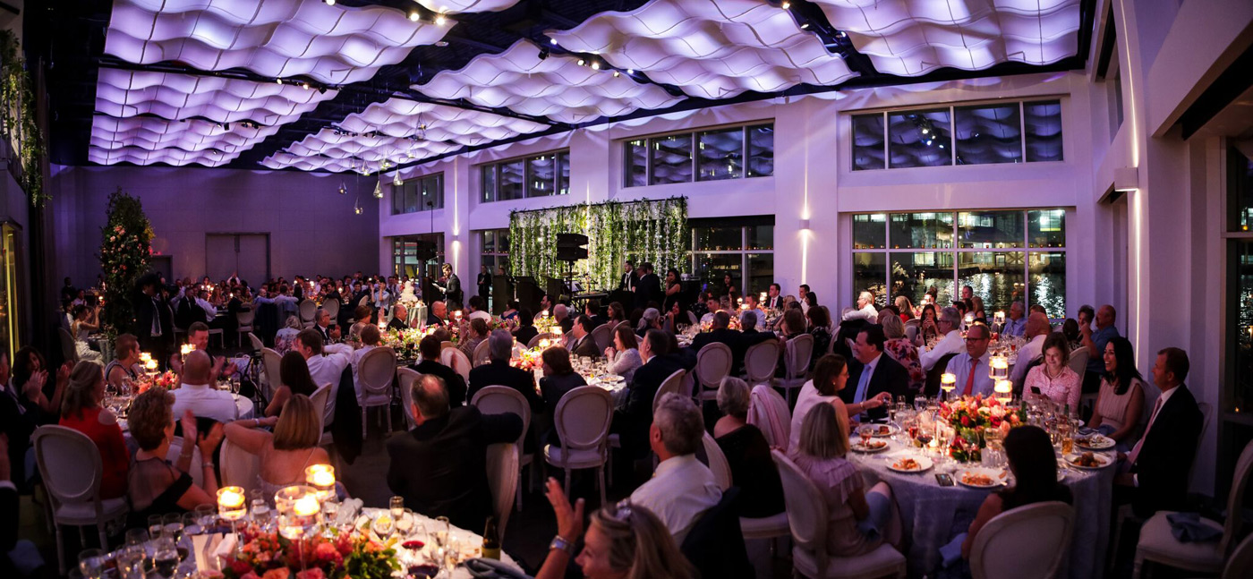Panoramic view of guests eating dinner at wedding.