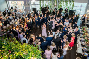 Bridesmaid in center of circle of guests on dance floor.