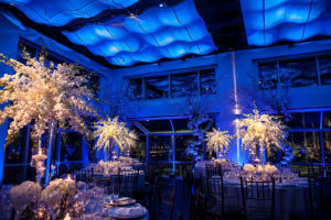 Tables set with floral centerpieces in blue-lit room