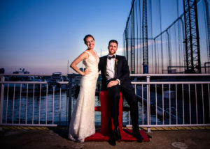 Bride and groom pose at railing along waterfront