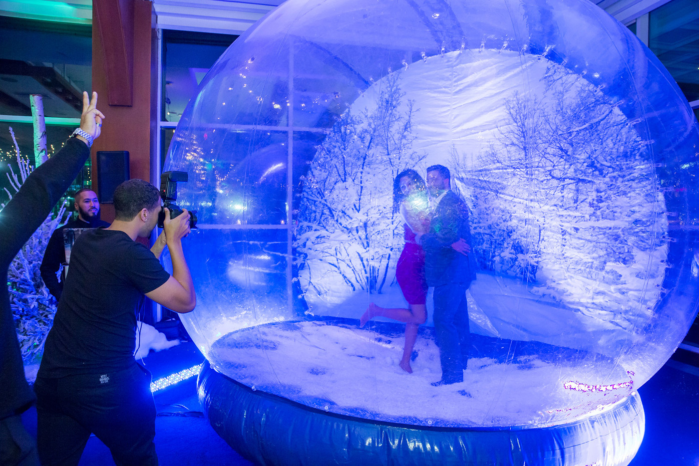 Couple having their picture taken inside giant snow globe