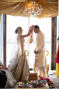 Bride placing floral necklace on groom in traditional Indian wedding