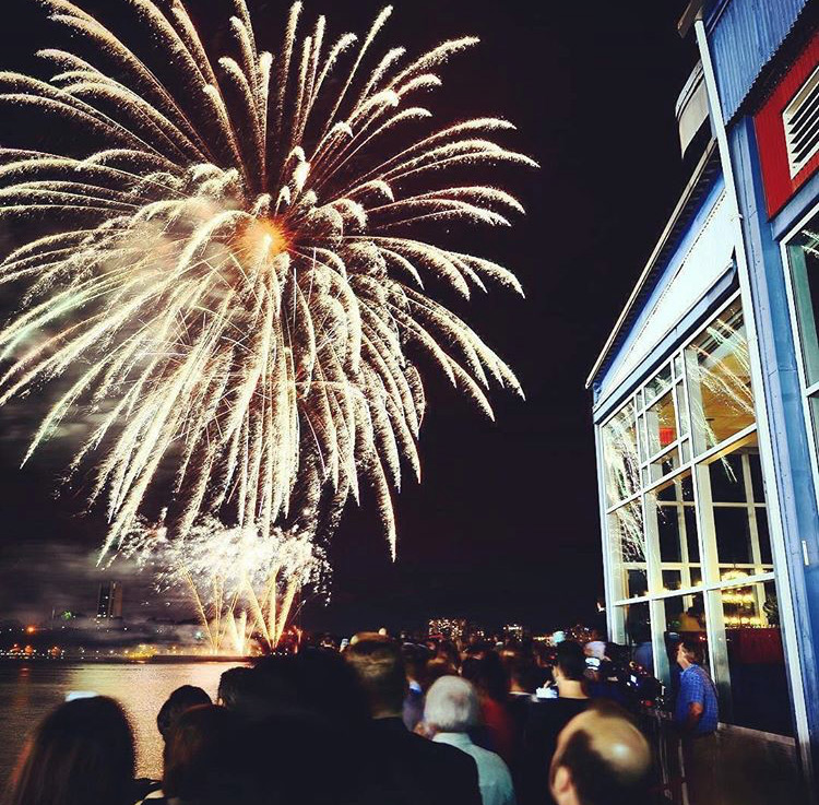Guests watch fireworks explode over water