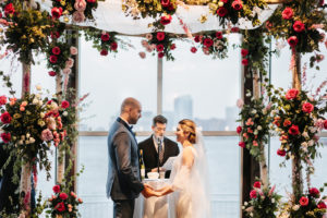 Officiant performs wedding ceremony as couples hold hands