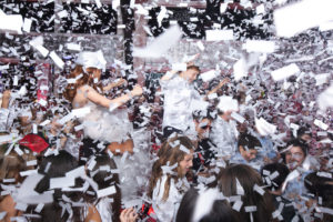 Crowd celebrating on dance floor with confetti flying in the air.