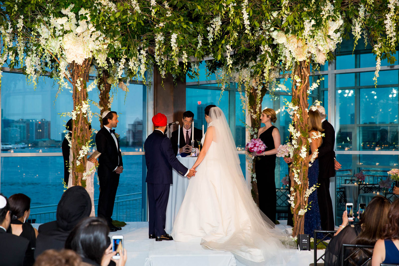 Officiant performing wedding ceremony under white flowers
