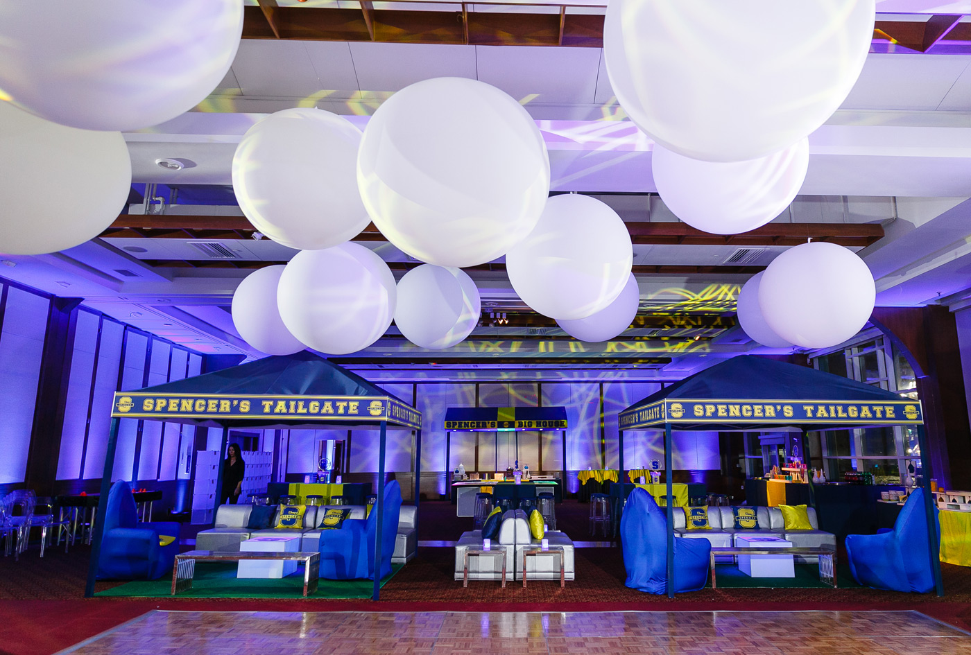 Giant white balloons hang above dance floor at tailgate themed Mitzvah