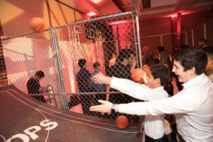 Boys in white dress shirts delighted by basketball arcade game.