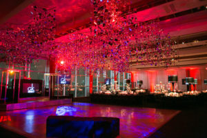 Glittery decorations hang above dance floor in red-lit venue.