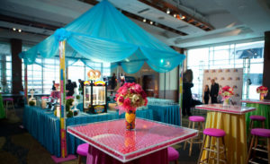 Gumball filled columns hold up blue tent with pretzel machine underneath.