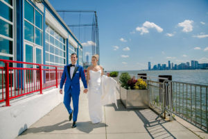 New couple holds hands as they walk along waterfront at Pier Sixty on clear sunny day.