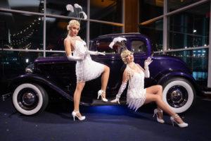Flapper girls posing beside classic car