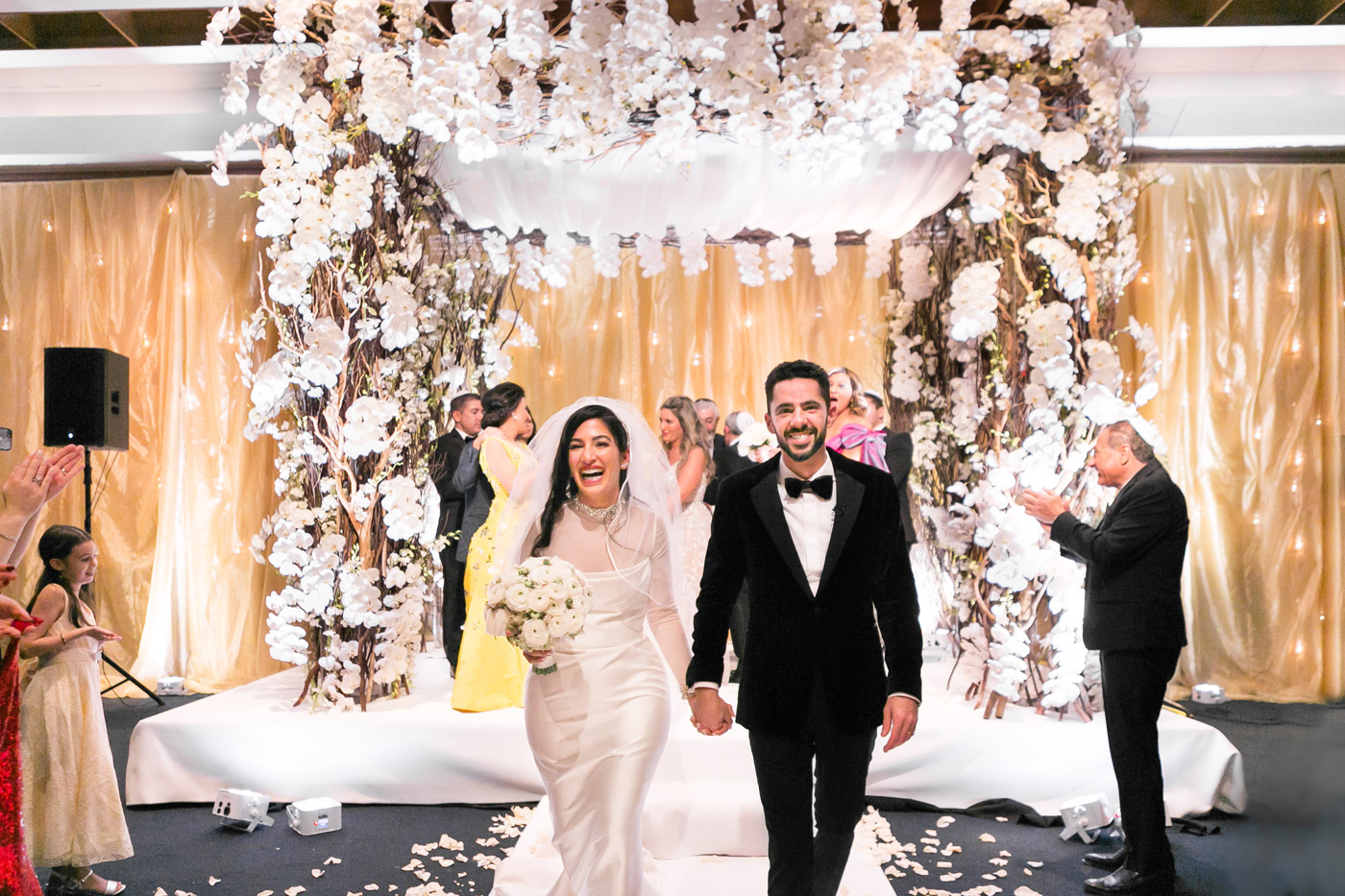 Couple smiles at camera as they walk back down aisle after wedding ceremony.