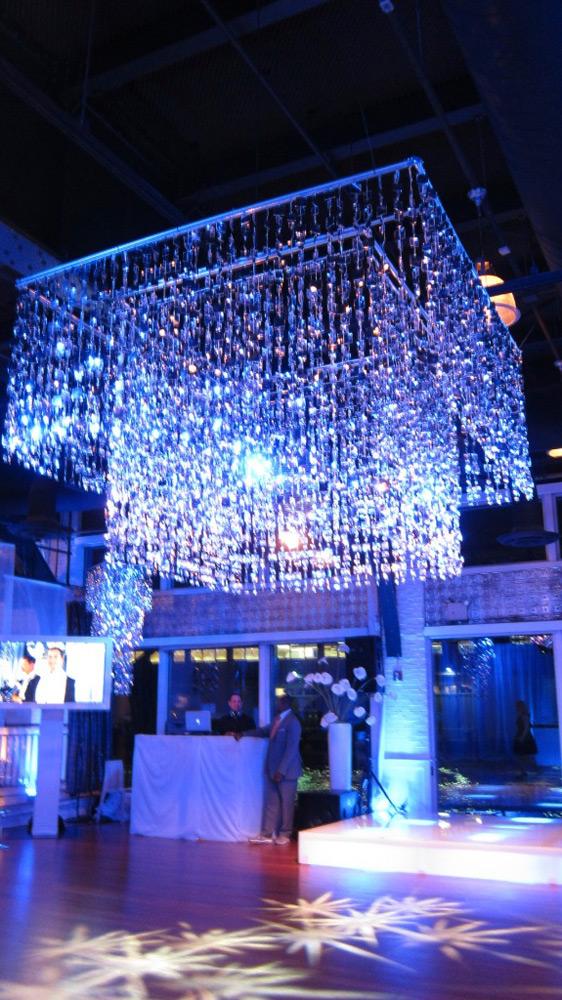 Giant, geometric crystal chandelier hanging above dance floor.