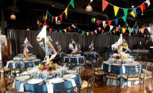 Colorful banners in air above baseball-pennant decorated dinner tables.