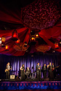 7 person band plays underneath colorful, exotic fabric decorations.