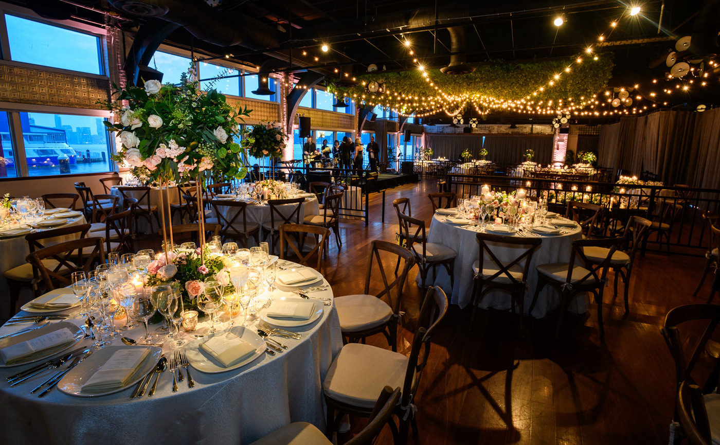 Tables set with floral centerpieces under decorative lighting