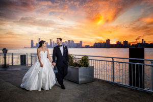 Bride and Groom walking on The Lighthouse veranda, the Hudson river, New Jersey and the Sunset are in the background