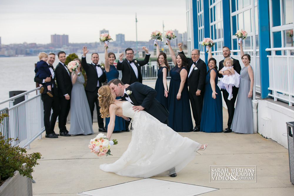 Bride and Groom Kissing in the veranda with bridal party behind
