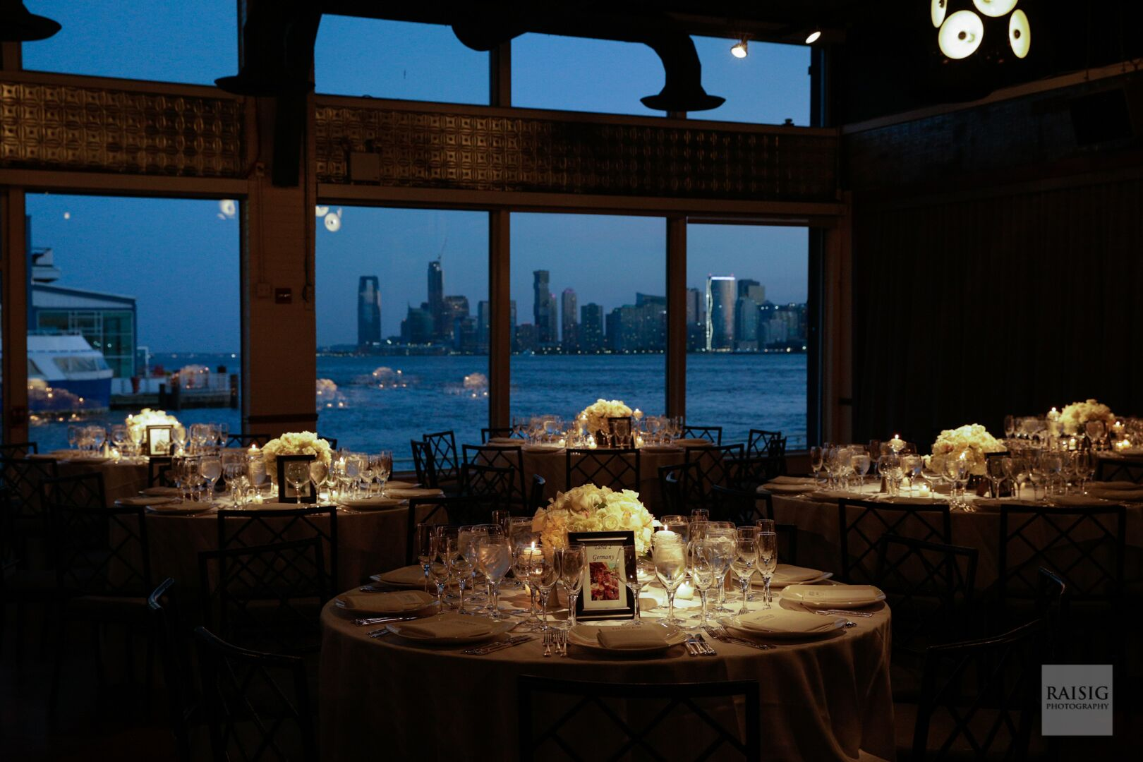 dinner tables with stunning view in the background of the Hudson River and New Jersey Skyline at dusk