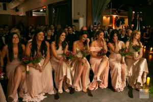 Bridesmaids on the first row wearing soft pink matching dresses