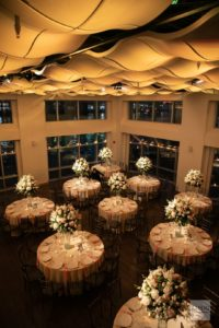 Current Pictures taken from above of the wedding ballroom set for dinner with amber lighting