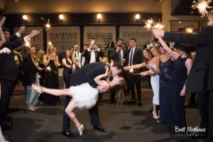 Bride and Groom having a Hollywood Kiss, Bridal party is behind them with sparklers