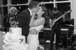 Bride and Groom by wedding cake kissing at Current