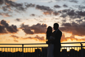 Bride and Groom at the lighthouse veranda over sunset