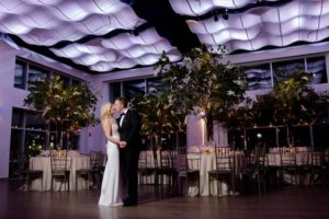 Bride and groom kissing in the ballroom by dinner tables